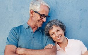 Older couple from San Diego showing off their respective All on 4 and All on X denture implants.